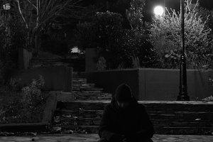 Man Sitting In Park At Night
