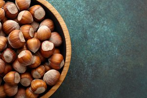 Hazelnuts in wooden bowl on textured