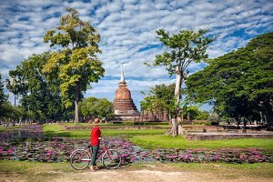 Woman with bicycle near temple in Th