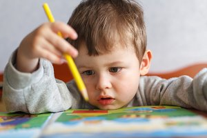 Little boy drawing with color pencil