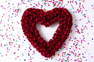Heart made of red roses and confetti