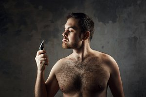 Hairy man with a naked torso holding