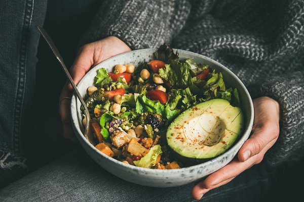 Woman holding bowl with fresh salad