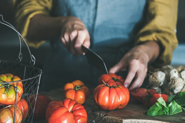 Woman in apron cooking tomato sauce