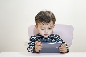 Little boy looking at smart phone sc