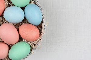Pastel dyed eggs in a basket on a wh