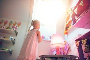 Little girl looking through window i