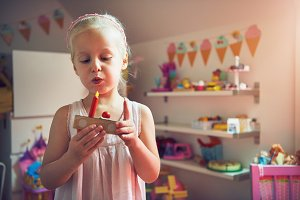 Girl blowing to candle on toy cake
