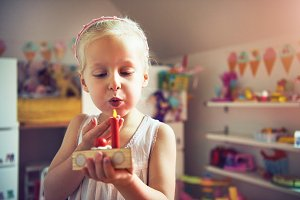 Cute girl blowing to red toy candle