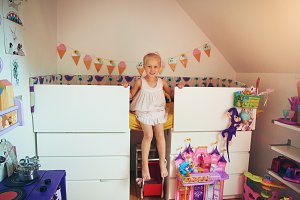 Cute little girl sitting on her bed
