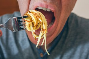 Man eating spaghetti with worms