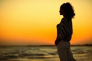 modern woman on beach in evening loo