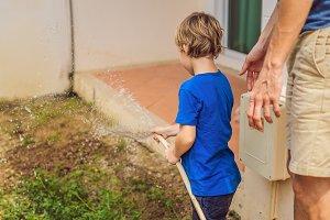 Cute little toddler boy watering