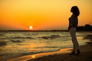 modern woman on seacoast in evening