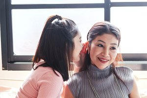 Teen daughter whispers to her mother