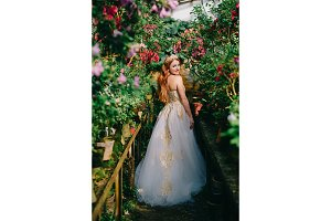 young happy bride stands in flowered