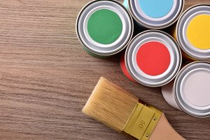 Colored paint pots and brush on wood
