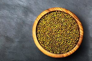 Dry green mung beans in a wooden bow