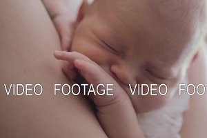 Newborn baby sleeping in mothers