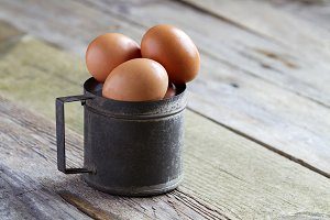 Fresh eggs in a metal cup