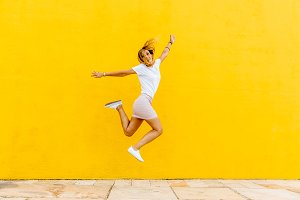 Happy girl jumping on a yellow backg