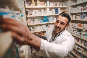 Pharmacy store owner checking stock