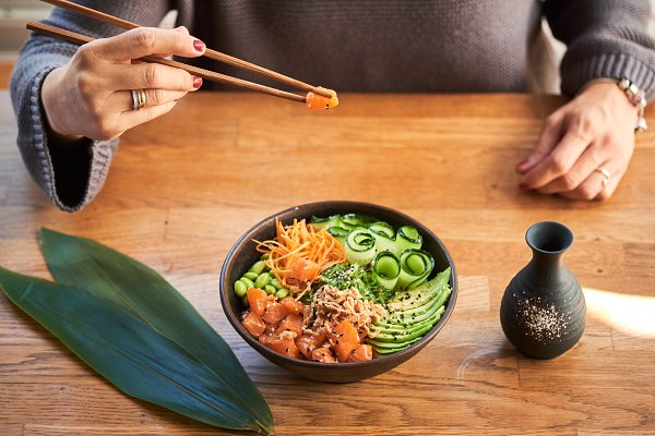 Woman eating poke bowl
