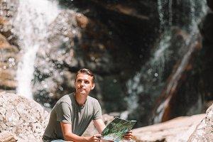 Man enjoying view of waterfall in gu