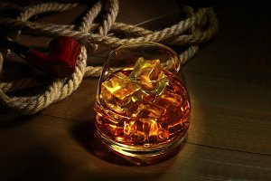 whiskey with ice cubes on wooden
