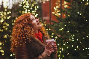 Girl with warming drink. Festive