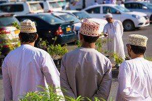 Three Omani men shoulders in traditi