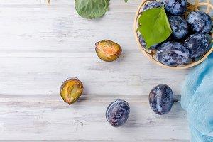 Fresh picked plums in a wicker vase