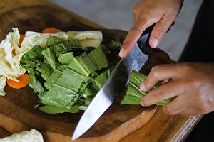 hand with knife cuts green onions