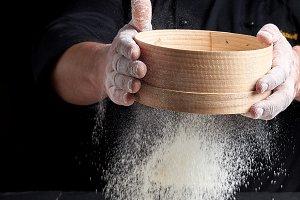 man sifts white wheat flour