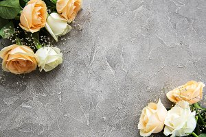 Yellow and white roses on a stone ba