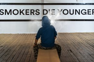 Teenager smoking and message on wall