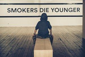 Teenager smoking and message on wall