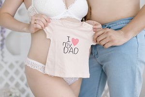 Future parents hold clothes for baby