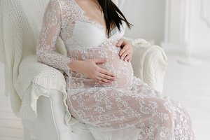 Pregnant young woman caressing belly