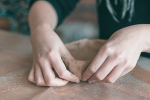 Ceramist hands make plate of clay