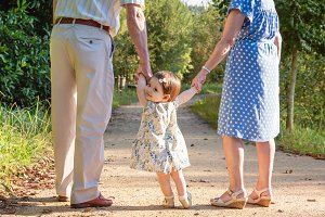 Baby girl walking with grandparents