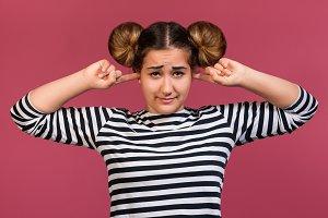 Unhappy girl closing ears, isolated