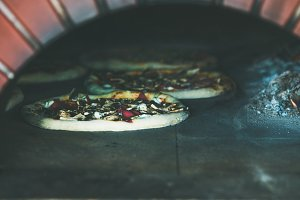 Baking pizzas with cheese and meat