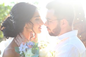 Bride and groom kissing in the park.