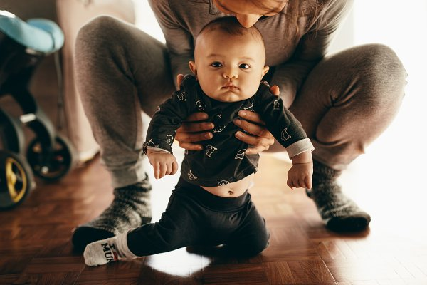 Mother squatting on floor