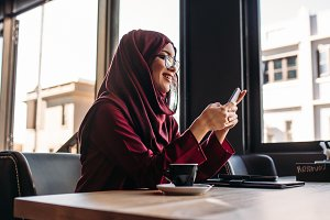 Woman in hijab sitting at cafe