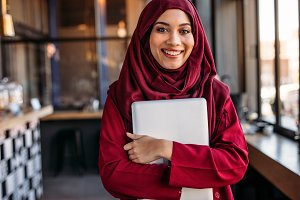 Muslim female standing with laptop
