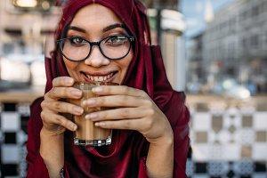 Smiling woman hijab having coffee