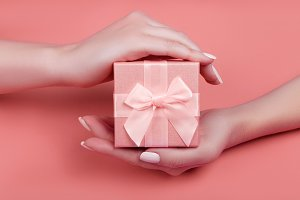 Hand woman holding pink gift box