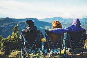 three friends sit in camping chairs